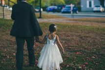 father and daughter walking holding hands
