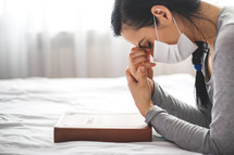 Woman with mask praying next to bed with her bible near.
