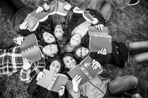 teens in a youth group lying in the grass reading Bibles