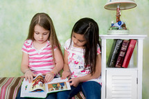 Two girls reading a Bible story.