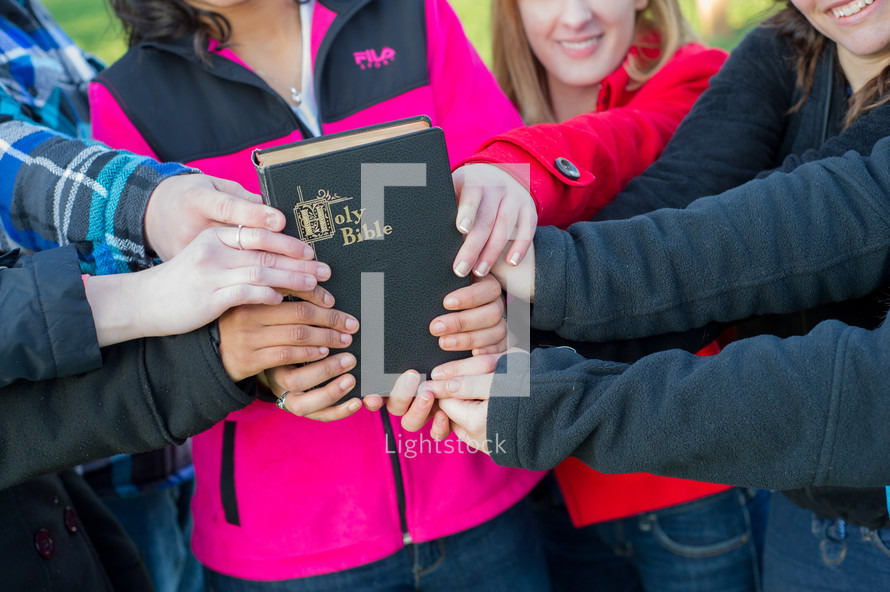 youth group members holding onto a Bible