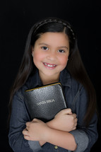 A young girl holding a Bible close to her heart