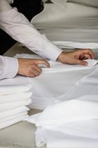 Hands folding napkins.