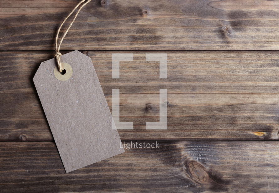 paper gift tag on wood background