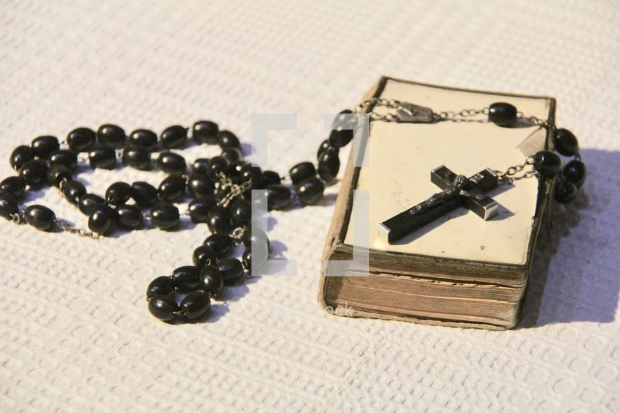 Rosary prayer beads on an old Bible