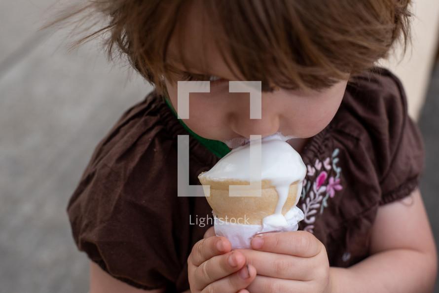 toddler girl eating an ice cream cone