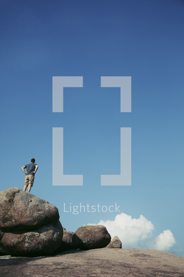 man standing on top of a rock