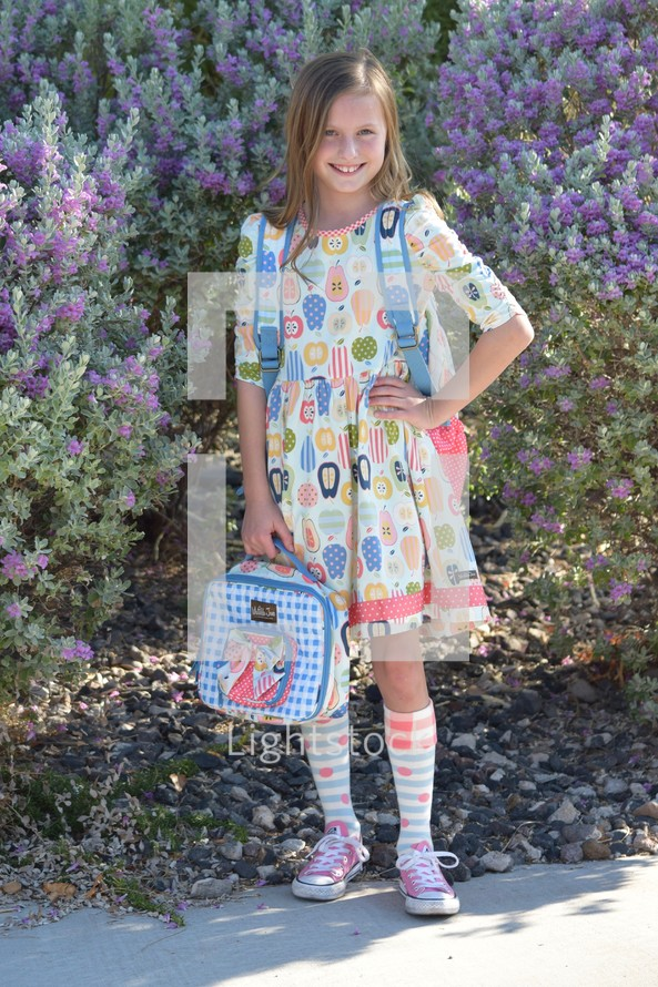 cute kid student waiting at the bus stop on the first day of school - back to school