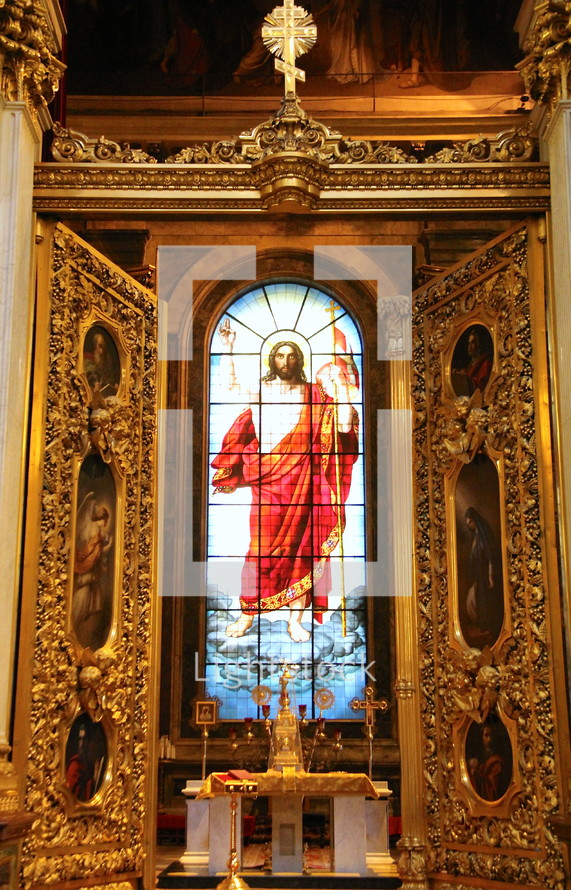 stained glass window of Christ behind an altar