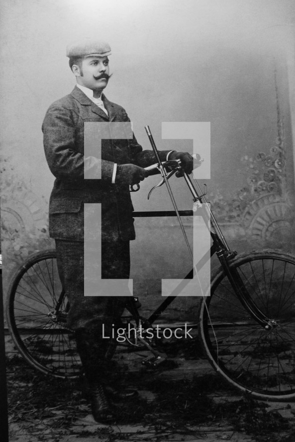 a vintage photograph of a man with a bicycle black white