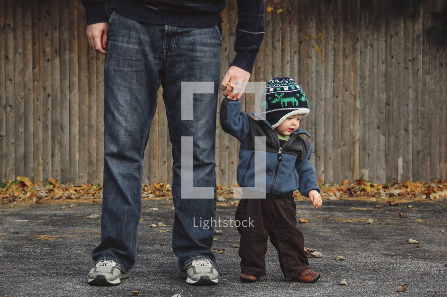 father and toddler son holding hands