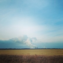 smoke from distant factories across a field