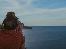 a woman with binoculars overlooking Nelson Bay