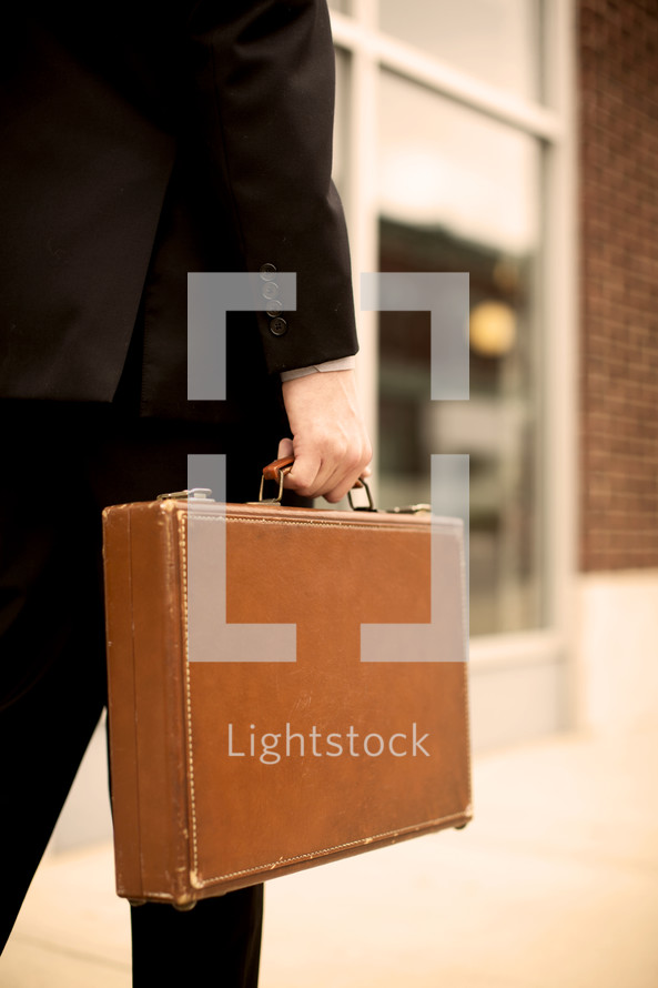 man walking carrying a briefcase