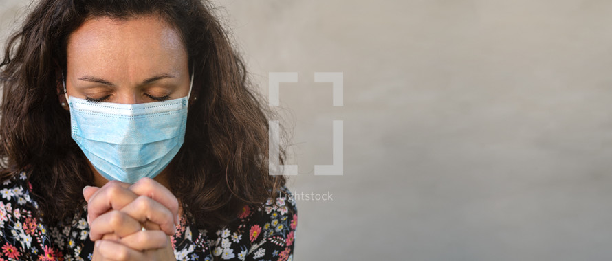 Christian worship and praise. A young woman is praying and worshiping with protection mask. Worship and prayer banner.