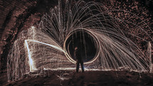 A man making a ring of sparks and light.