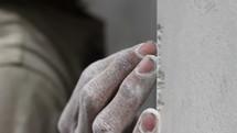A man sanding a wall