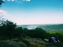 a couple sitting on a mountain top looking out