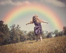 a child running under a rainbow