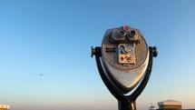 A seagull flies by a binoculars stand.