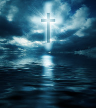 Light shining from behind a cross above water