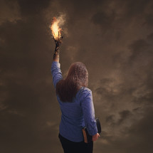 Woman holding a bible with a flame of fire coming from her extended hand.