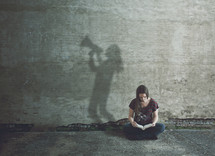 A woman reading a Bible and her shadow making an announcement in a megaphone