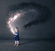 A little girl looks at a cell phone that has a dark monster