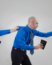 man with a Bible being held back