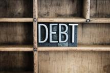 word debt in blocks on a shelf