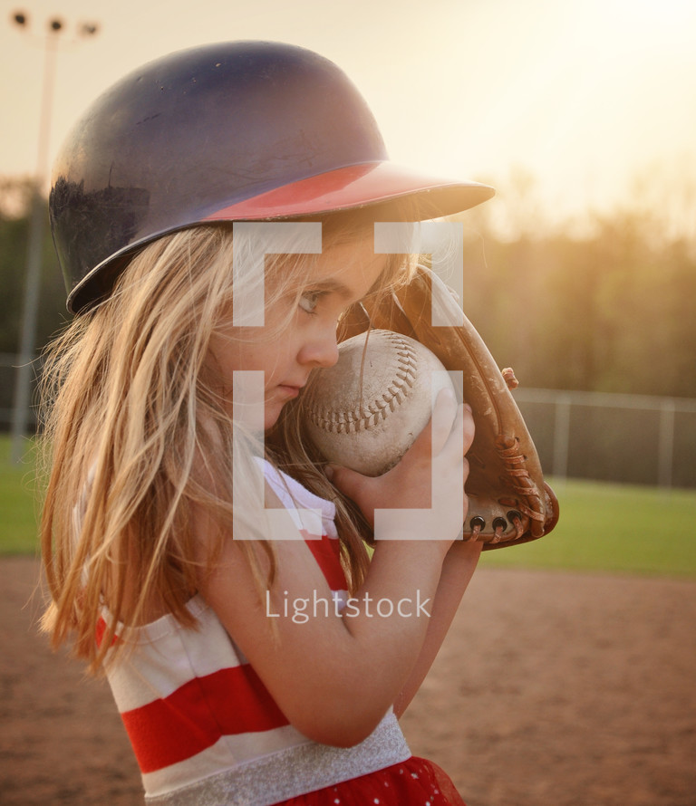 a little girl playing baseball