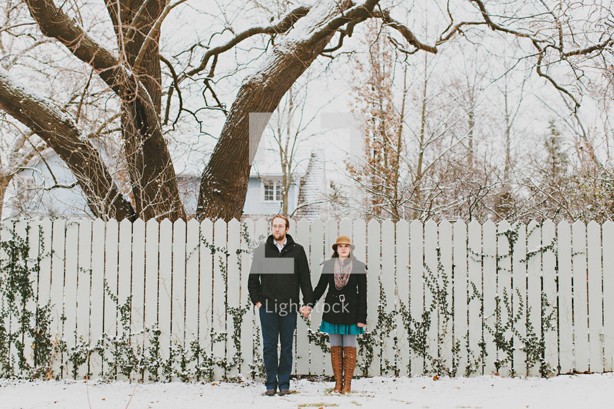 a couple standing in front of a fence in the snow holding each others hands