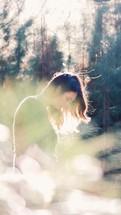 A woman standing outdoors under intense sunlight.