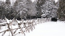 falling snow along a fence line
