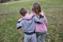 A young boy and girl walking with their arms around each other.