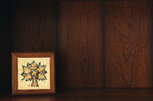 tile mosaic from Jordan on a wooden bookshelf