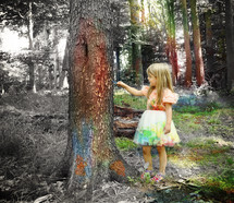 a girl painting a tree