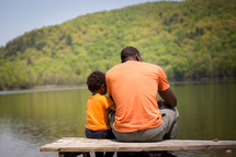 father and son sitting on a bench by a pond