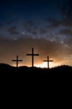 sun setting behind three crosses