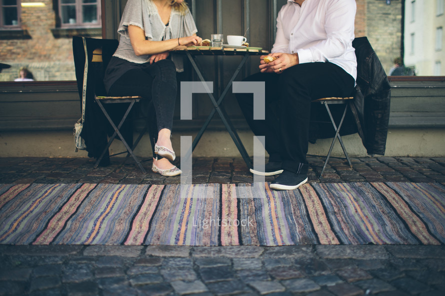 A man and woman sitting at a table drinking coffee