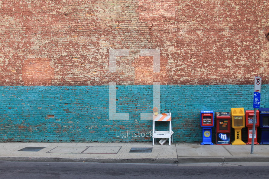 construction zone sign and newspaper stands in front of a brick wall