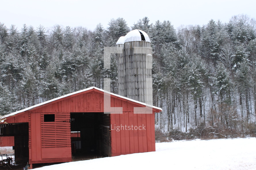 red barn and silo and snow on the ground