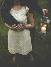 Couple embracing while holding a candle light.