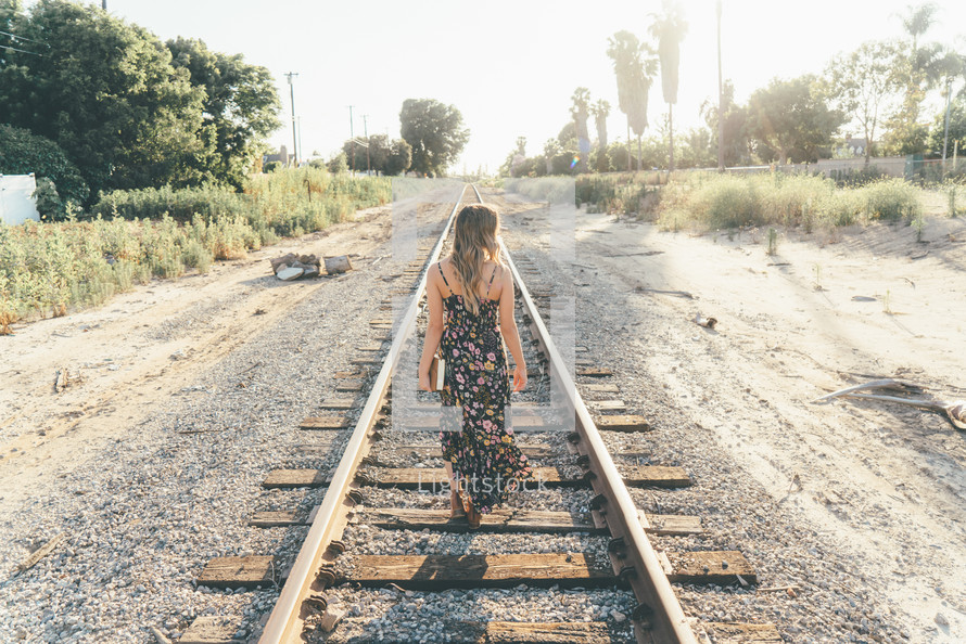 A girl walking down an abandon railroad track and holding her bible.