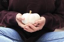 a woman holding a white pumpkin