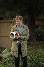 a young woman in a coat holding a Bible outdoors