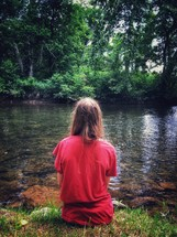 a girl sitting on a riverbank