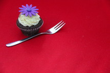 Cupcake decorated with cream cheese, sprinkles and fondant purple flower against a red background.