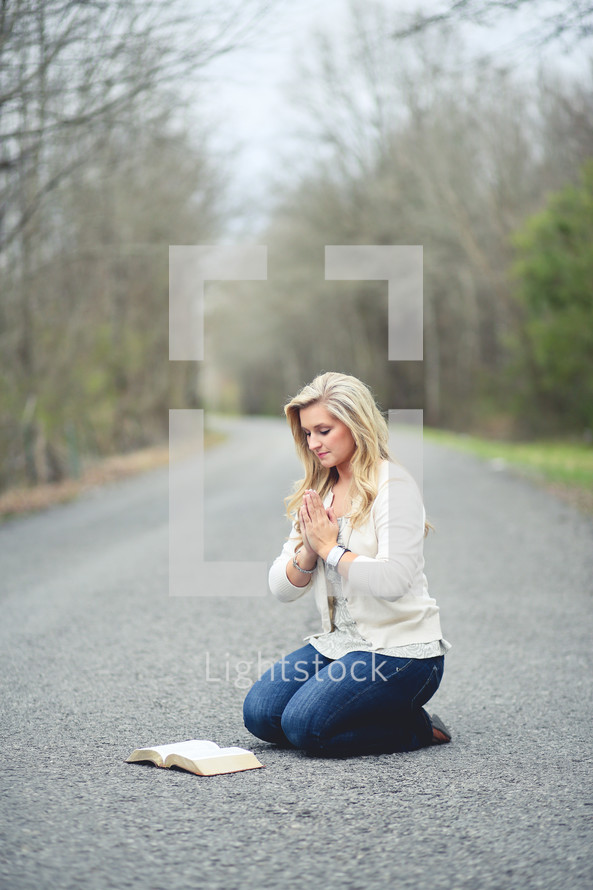 woman kneeling in prayer in the middle of a road next to an open Bible