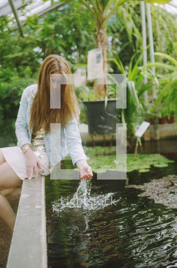 a woman dipping her hand in water in a fish pond